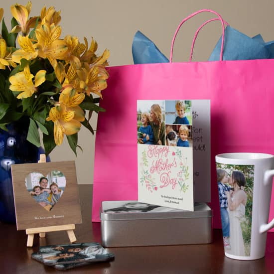 Flowers in vase, large gift bag, photo tile, tin, blank card and mug on table