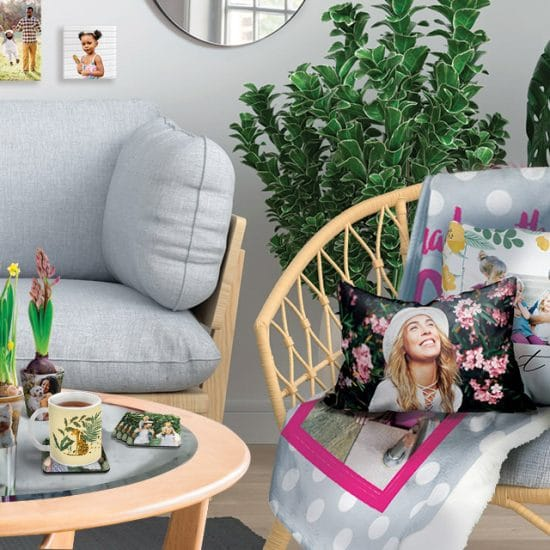 living room with pillows, blanket on chair, canvas on wall, photo boook, plant pot, coasters and mug on table.