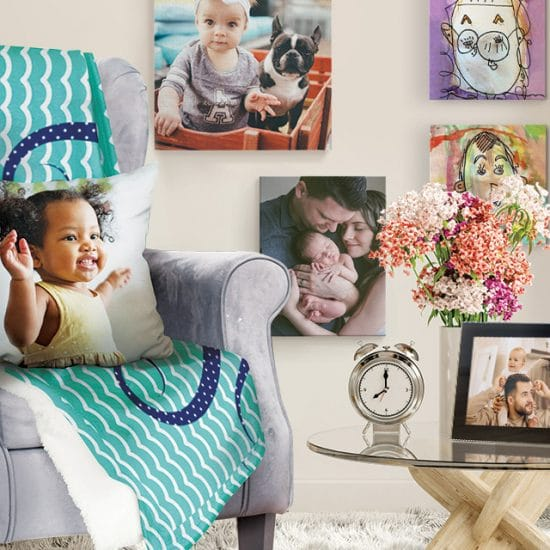 chair draped with a blanket and pillow, canvases on the wall, and a framed print on coffee table